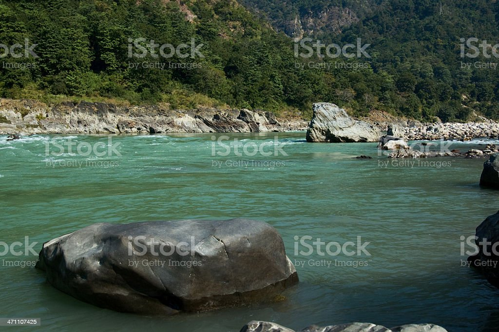Huge rock in the river ganges with mountains royalty-free stock photo