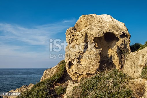 istock Huge rock strange form with holes. The desert landscape with prickly bush, sea and blue sky. 1129333035