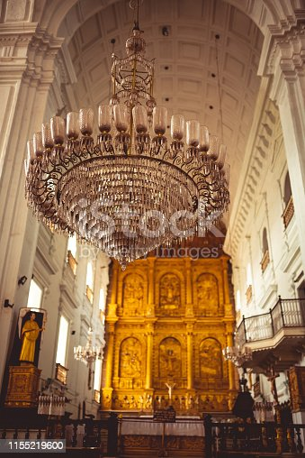 Huge round glass chandelier for candles hands in the middle of an old church and main area with statues and old carvings in the background.