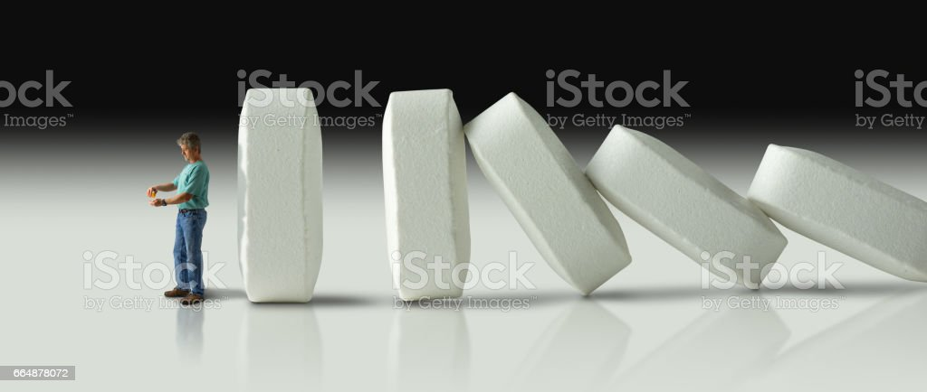 Huge row of pills crashing over like dominoes to eventually crush the man with pain pill addiction stock photo
