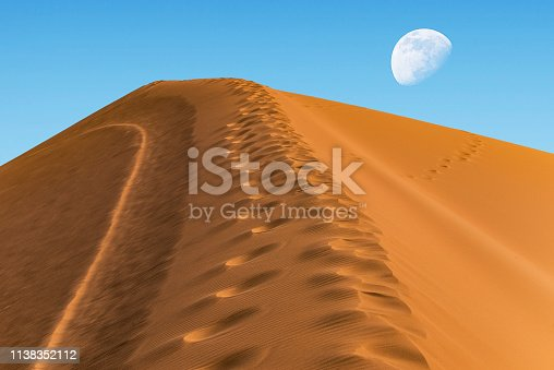 huge sand dune on the background of the sky with a moon on the horizon