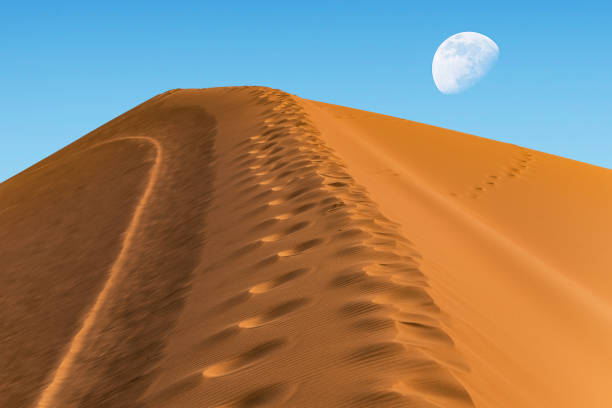 huge sand dune on the background of the sky with a moon on the horizon stock photo