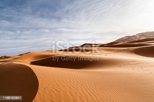 Orange dunes and cloudy sky in Sahara desert. Sunrise in the desert.