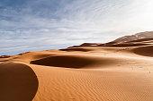 Orange dunes and cloudy sky in Sahara desert. Sunrise in the desert.