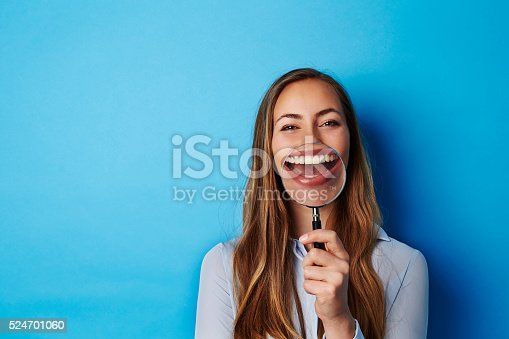 istock Huge smile through magnifying glass of young woman 524701060