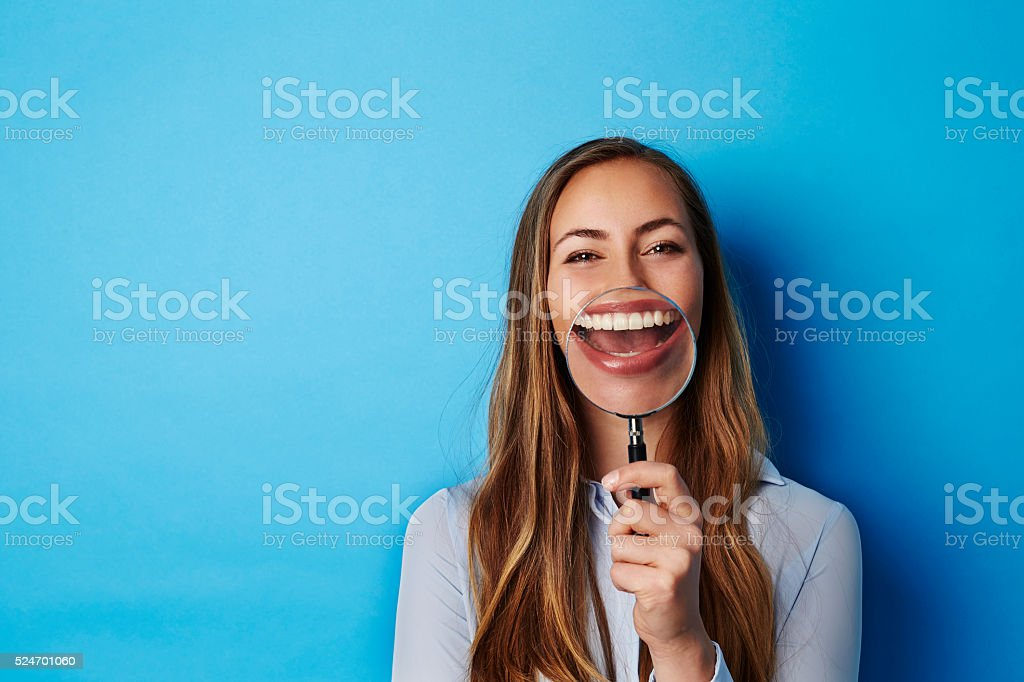 Huge smile through magnifying glass of young woman stock photo