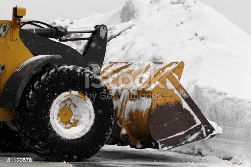 A front end loader lifting a bucket full of snow from a parking lot onto a snow bank. Lots of small falling snow flurries throughout the frame.