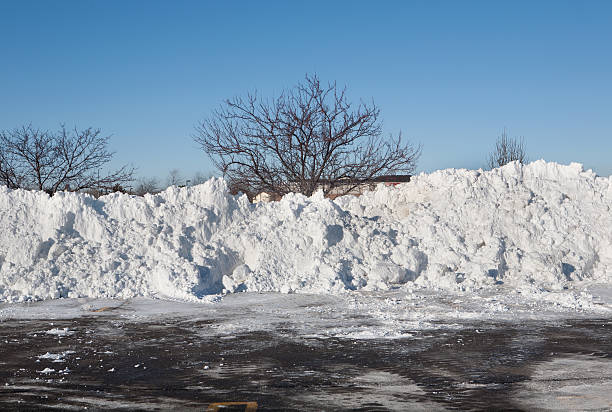 huge snowpiles in plowed parking lot stock photo