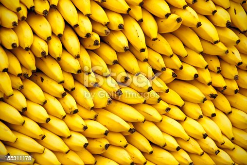 Full frame closeup of wall of bananas at fruit vendor. Great for backgrounds, backdrops, or puzzle.