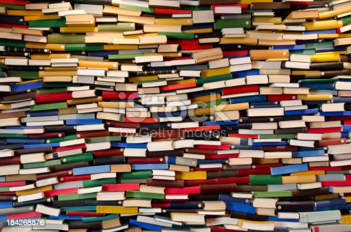 A lot of books stacked and forming a wall.