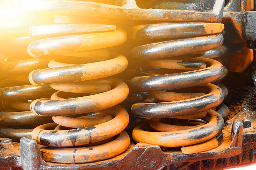 Huge steel spring shock absorbers black and rusty close up.