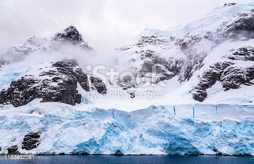 Huge steep stone rock covered with blue glacier and cloud with water in foreground, close to Argentine islands, Antarctic