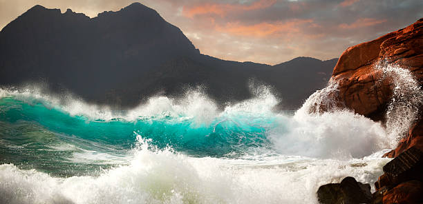 Huge Storm Surf Huge storm waves crashing on the rocks. Location: Porto, west coast of Corsica, France. rocky coastline stock pictures, royalty-free photos & images