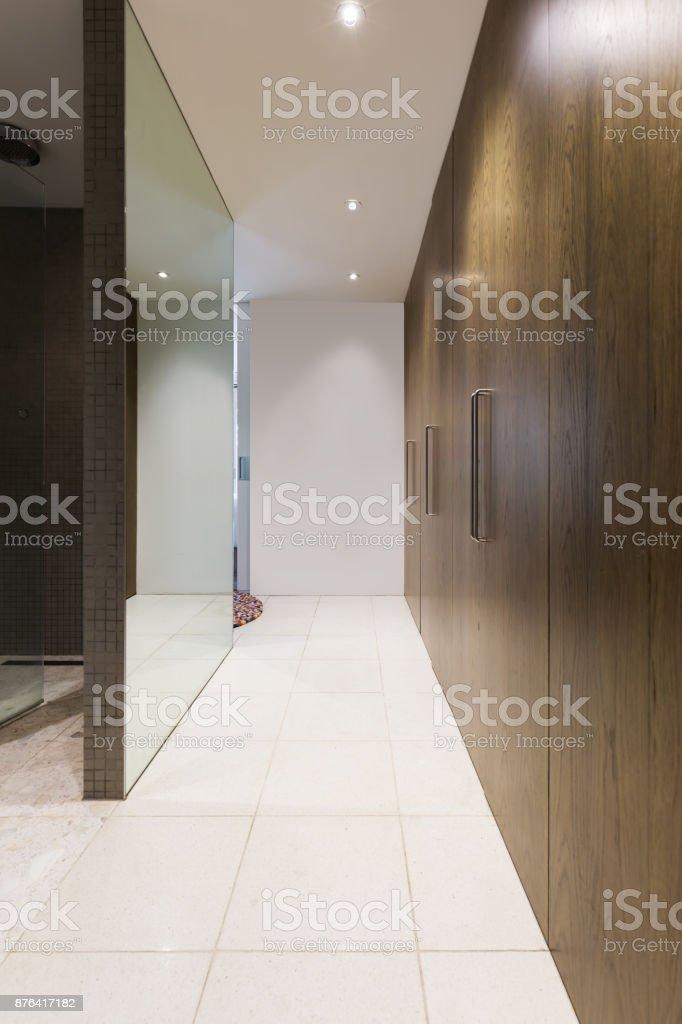Huge walk through wardrobe with walnut doors hallway in luxurious Australian home stock photo