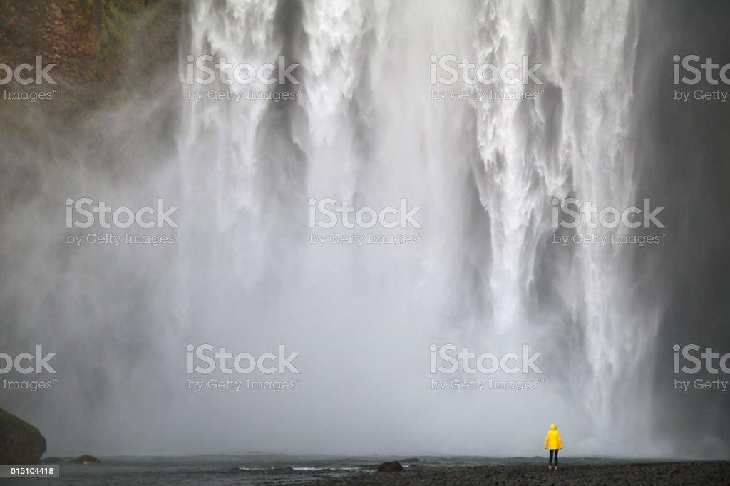 Huge waterfall and person in yellow jacket stock photo