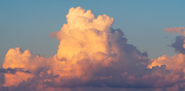 A huge white-pink volumetric cloud in the blue sky.