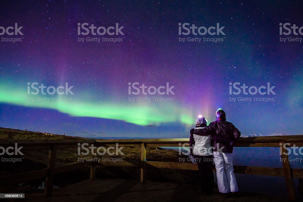 Hugged couple gazing to Northern lights Aurora Borealis in Iceland stock photo