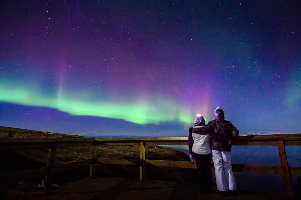 Hugged couple gazing to Northern lights Aurora Borealis in Iceland stock photo