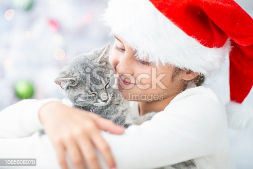A cute little girl with brown hair wearing a santa hat, hugs her kitten. They both look loving and sweet.