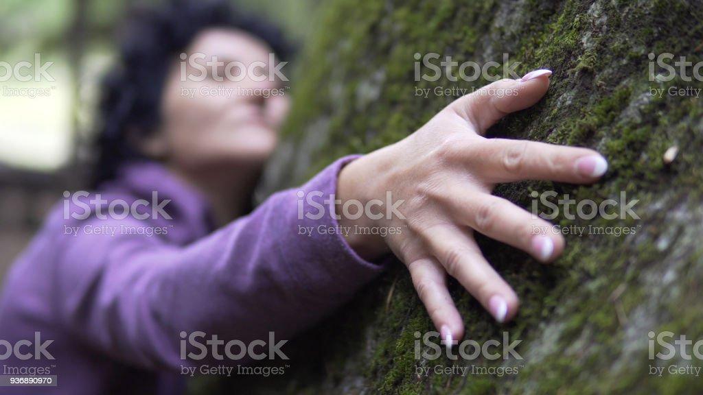 Eine Natur umarmt. Eine Frau legt ihre Arme um großen Stein mit Moos, den Austausch von Emotionen und Energie aus der Natur laden. – Foto