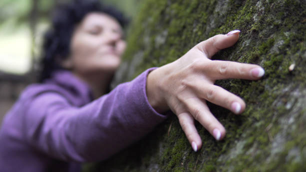 Hugging a nature. A woman puts her arms around large stone with moss, exchanging emotions and charging energy from nature. Hugging a nature. A woman puts her arms around large stone with moss, exchanging emotions and charging energy from nature. tree hugging stock pictures, royalty-free photos & images