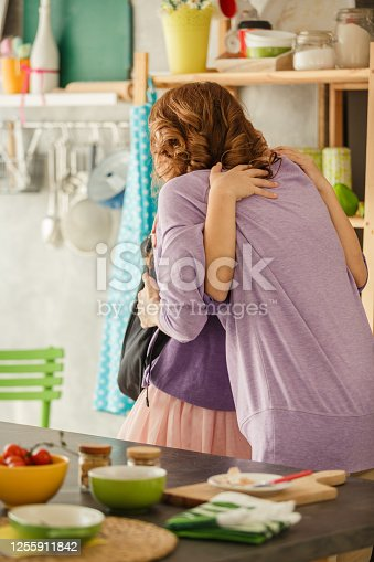 Happy mother and daughter hugging before going to school, after mother made and packed lunch for her daughter.