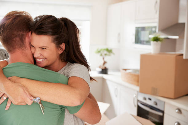 hugging couple celebrating moving into new home - house hunting stock photos and pictures