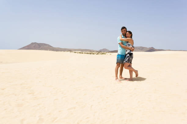 Hugging couple posing at empty sand dunes in Corralejo Natural Park stock photo