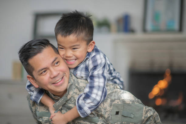 Hugging Dad A military dad and his son are hugging in their living room. The son is smiling happily at the camera. filipino ethnicity stock pictures, royalty-free photos & images