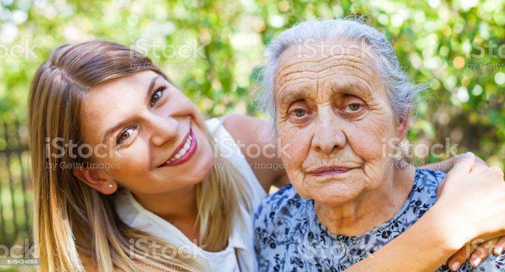 Hugging grandma in the park stock photo