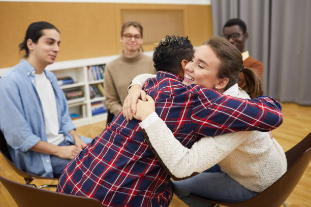 Hugging in Support Group Portrait of two young women hugging in support group meeting, both smiling happily, copy space drug rehab stock pictures, royalty-free photos & images