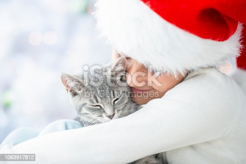 A young girl is wearing a Santa hat and cuddling her cute kitten.