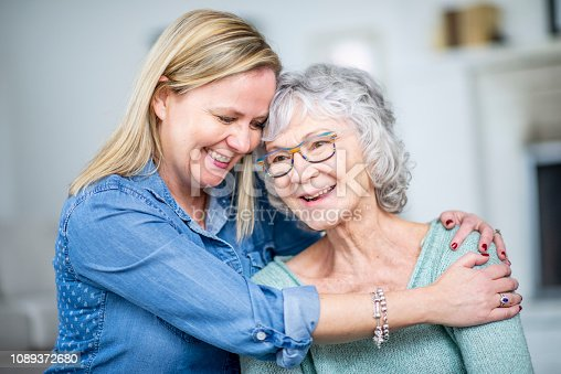 A woman and her grandmother are hugging and smiling while in their living room.