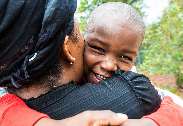 Hugging Mom Afro caribbean child hugging his mom haitian ethnicity stock pictures, royalty-free photos & images
