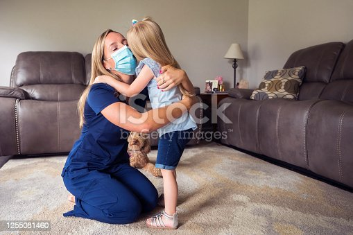 A 3 year-old girl hugs her Mommy after helping her put on a face mask before she leaves for work as a nurse, Indiana, USA