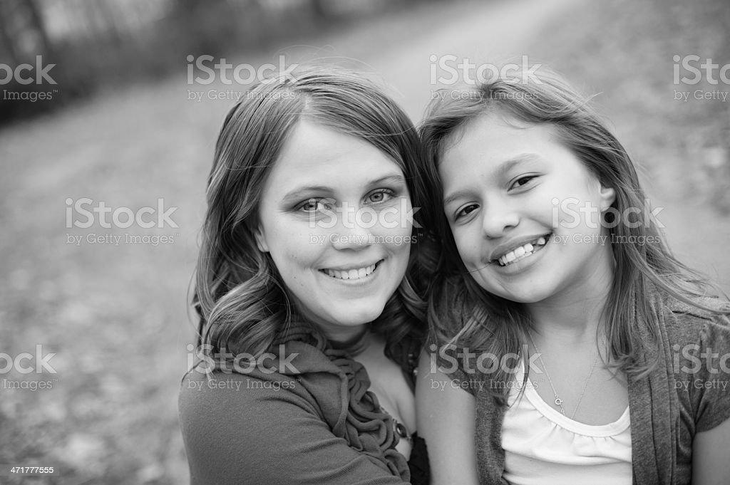 Hugging Sisters Sitting Outside in the Fall royalty-free stock photo