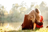 two young women sitting on grass hugging rear view