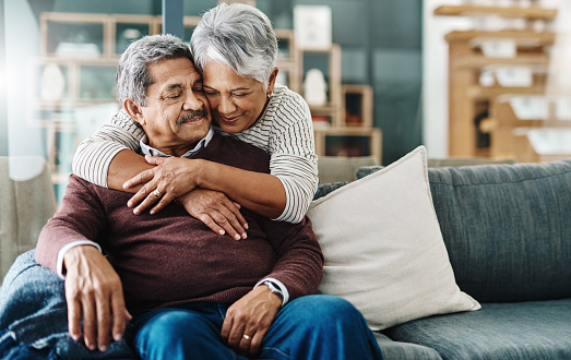 Cropped shot of a cheerful elderly woman hugging her husband who's in a wheelchair at home during the day