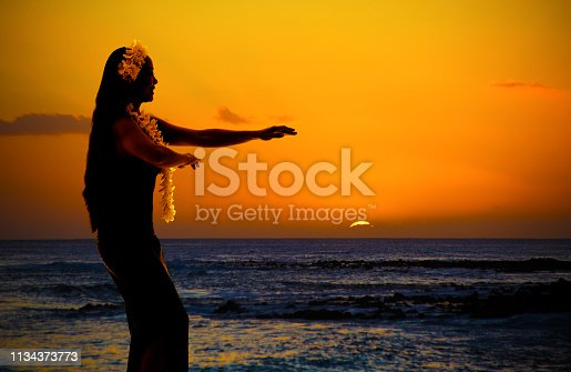 A Hula dancer dancing on the tropical beach of Hawaii at sunset. Photographed in Kauai, Hawaii.