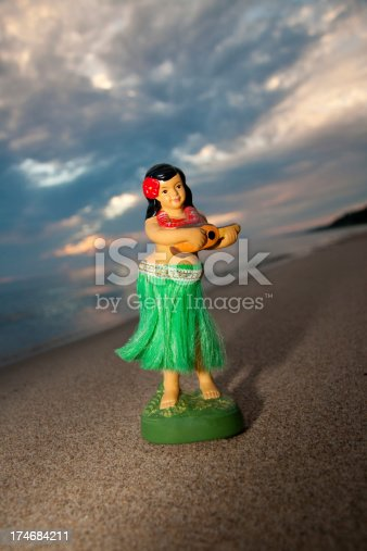 A Hula Dancer figurine on the beach at sunset with sunset shadows.