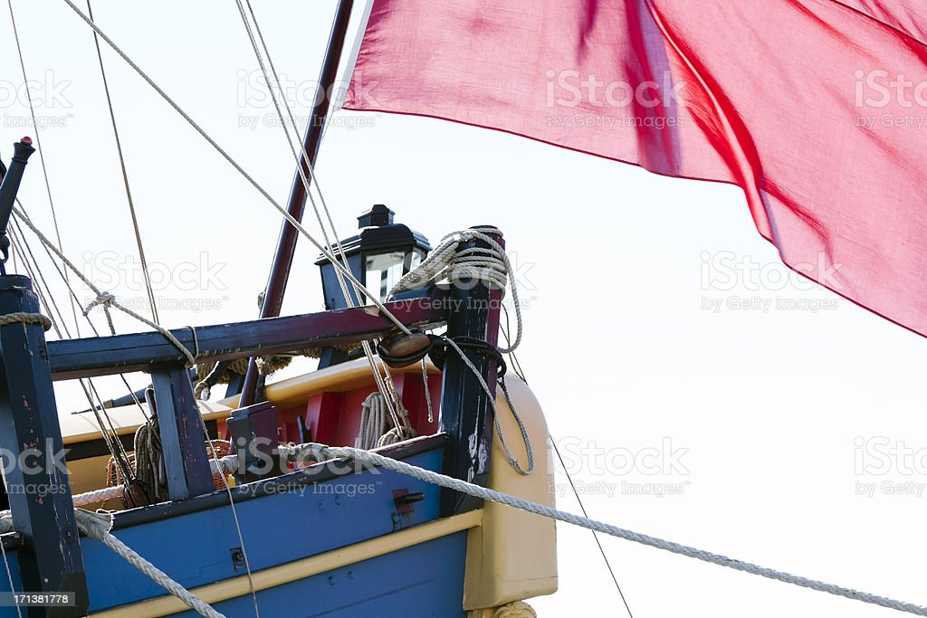 Hull of old sailing ship with red flag, copy space royalty-free stock photo
