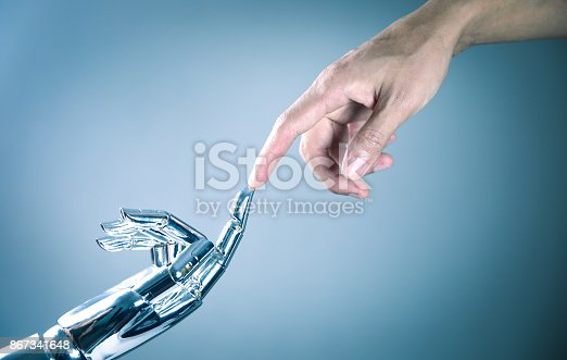 istock Human and robot hand connecting 867341648