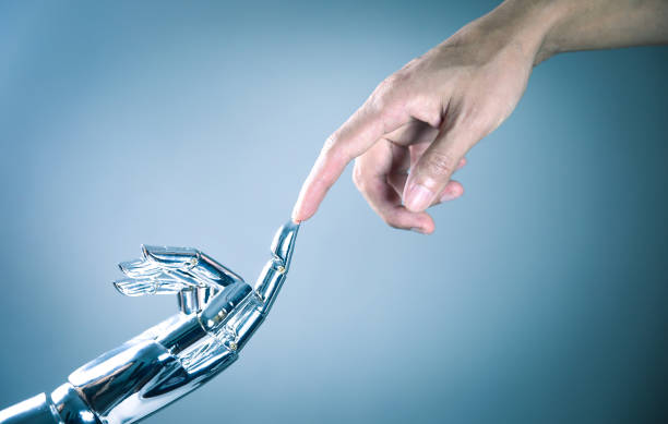 Human and robot hand connecting stock photo