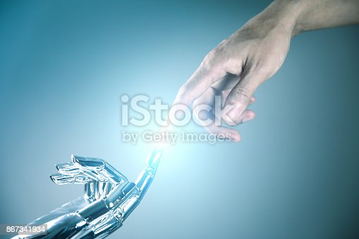 istock Human and robot hand connecting 867341934
