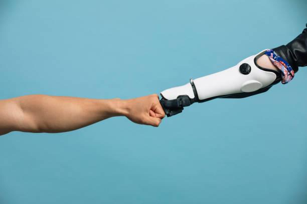 un brazo humano y robótico haciendo un golpe de puño - robot fotografías e imágenes de stock