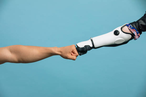 a human and robotic arm making a fist bump - cybernetic stock pictures, royalty-free photos & images