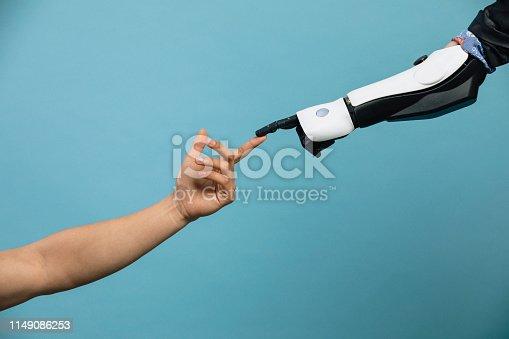 istock Human and Robotic Hand Touching 1149086253