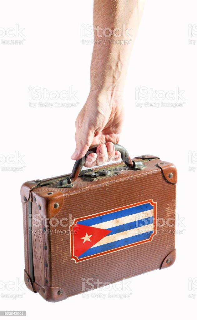 Braço humano, carregando uma mala antiga com bandeira de Cuba - foto de acervo