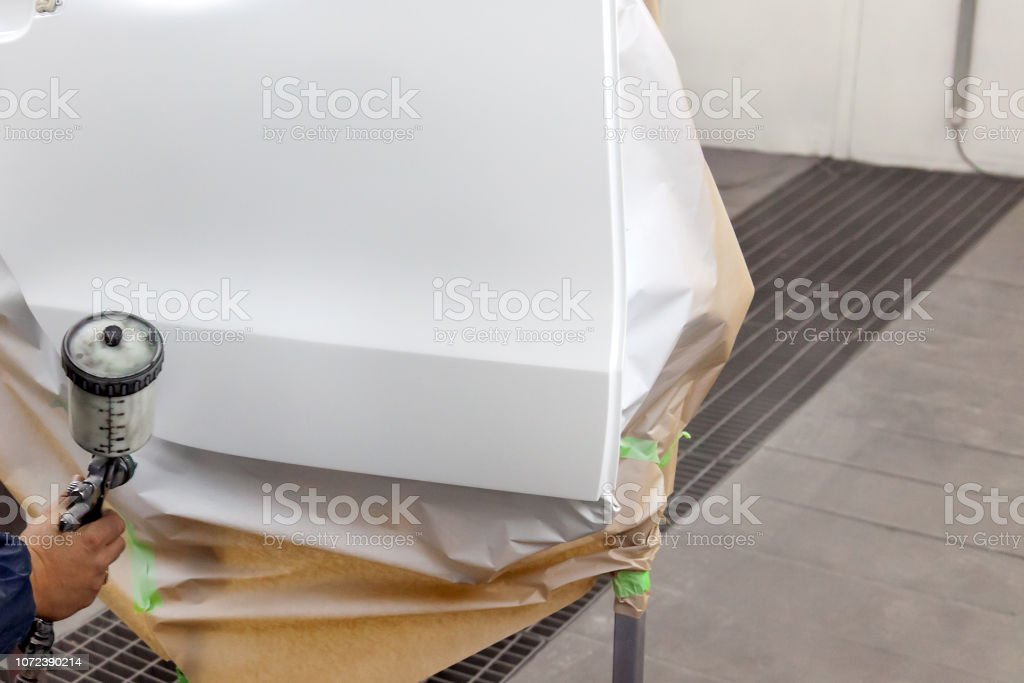 A human arm paints with a spray gun a part of the car body in white after being damaged during an accident. Door from the vehicle during the repair in the workshop. stock photo