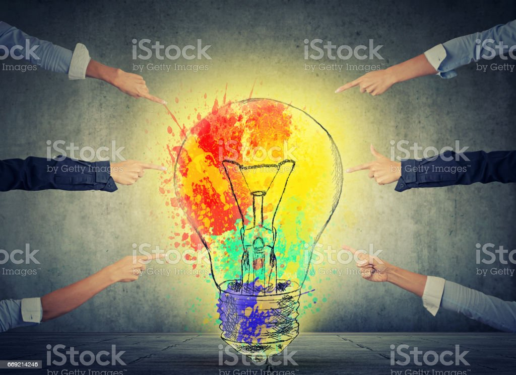 Human arms fingers point at bright idea colorful glowing light bulb stock photo